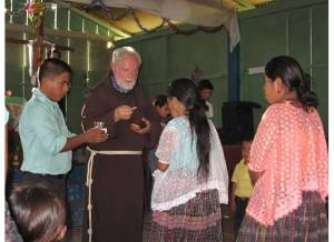 Fr. Emmet Murphy, a priest associated with St Francis of Assisi, celebrates communion with members of Las Margaritas II.